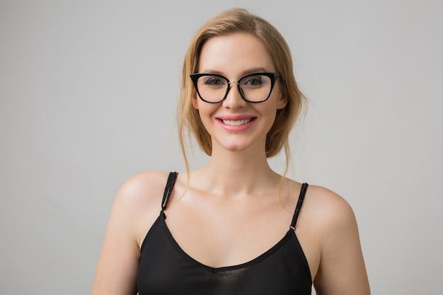 Szczegół portret młodej atrakcyjnej seksownej kobiety w stylowych okularach, inteligentny i pewny siebie, uśmiechnięty i szczęśliwy, czarna sukienka, elegancki styl, modelka pozowanie na tle białego studia, na białym tle