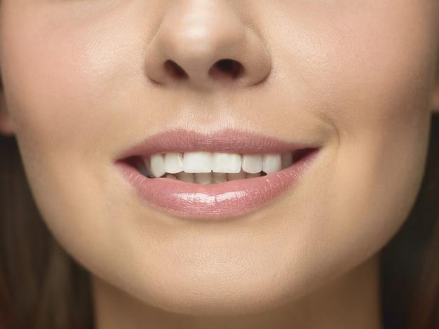Szczegół portret młodej kobiety twarz. modelka o zadbanej skórze i dużych, uśmiechniętych ustach.