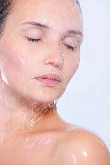 Szczegół portret młodej twarzy kobiety z pluskiem i kroplami wody
