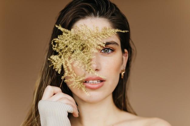 Szczegół portret modnej białej kobiety z zieloną rośliną. kaukaska dziewczyna debonair.