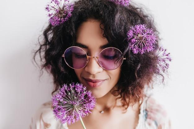 Szczegół portret modnej dziewczyny z czarnymi kręconymi włosami. entuzjastyczna afrykańska modelka z fioletowym allium.