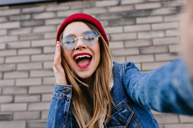 Szczegół portret oszałamiającej blondynki w dżinsowej kurtce, dzięki czemu selfie z uśmiechem. zdjęcie radosnej białej kobiety z wyrazem szczęśliwej twarzy spędzającej czas na świeżym powietrzu.