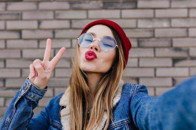 Szczegół portret pięknej białej dziewczyny w okrągłych okularach, wyrażające pozytywne emocje. fascynująca kobieta robi selfie z całowaniem wyrazem twarzy na ścianie z cegły.