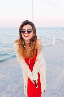 Szczegół portret pięknej dziewczyny w czerwonej sukience i białej kurtce na molo, uśmiechając się i słuchając muzyki na słuchawkach na smartfonie.