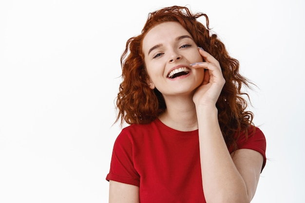 Szczegół portret pięknej imbirowej dziewczyny z bladą zdrową skórą, dotykając policzka i śmiejąc się, uśmiechając się, szczęśliwa, pozytywne emocje koncepcja, biała ściana