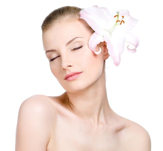 Szczegół portret pięknej kobiety zmysłowości z zamkniętymi oczami iz kwiatem we włosach - na białym tle