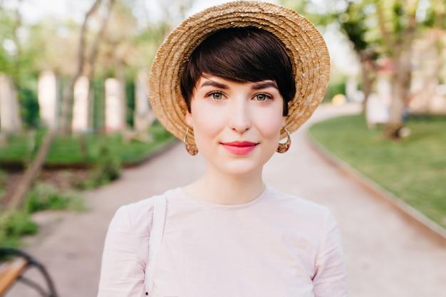 Szczegół portret pięknej młodej damy w słomkowym kapeluszu i uroczych kolczykach z naturalnym makijażem nago
