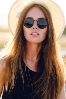 Szczegół portret pięknej młodej dziewczyny z długimi ciemnymi włosami na sobie słomkowy kapelusz i ciemne okulary przeciwsłoneczne. uśmiecha się lekko
