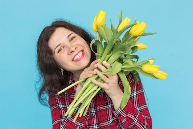 Szczegół portret pięknej młodej kobiety z żółtymi tulipanami na niebieskiej ścianie.
