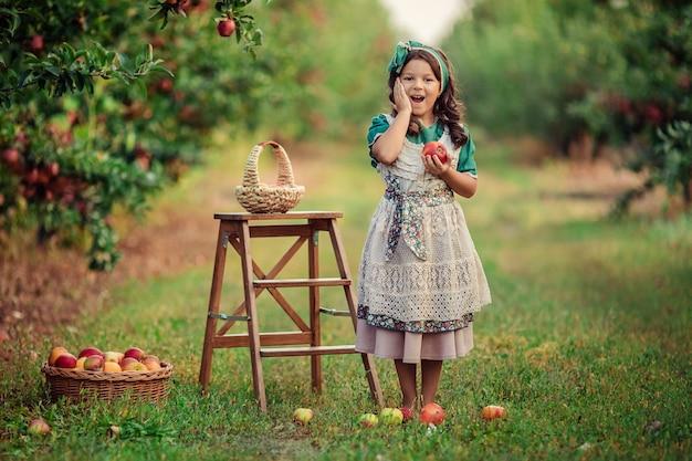 Szczegół portret pięknej ślicznej dziewczyny o ciemnych włosach z czerwonym jabłkiem w dłoniach w sadzie jabłkowym podczas żniw.