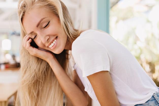 Szczegół portret podekscytowana opalona kobieta z prostymi długimi włosami pozowanie z czarującym uśmiechem. zdjęcie stylowej dziewczyny w białej koszulce śmiejącej się z zamkniętymi oczami.