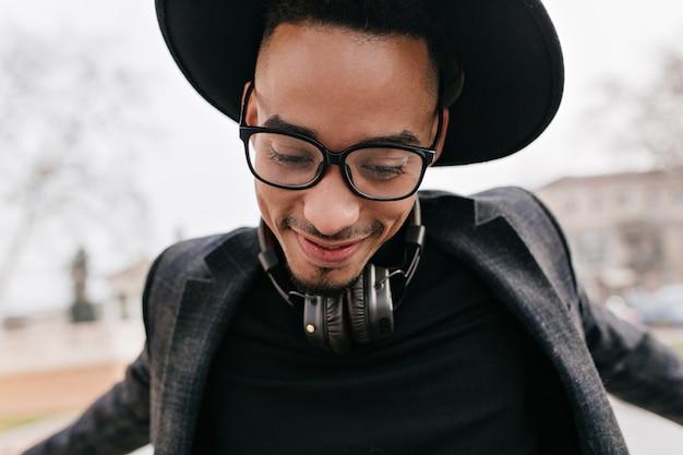 Szczegół portret podekscytowany facet z ciemną skórą, taniec na ulicy. zewnątrz zdjęcie dobrze ubranego modelu męskiego w kapeluszu i słuchawkach
