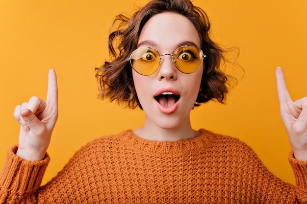Szczegół portret pozytywnej europejskiej kobiety nosi eleganckie żółte okulary przeciwsłoneczne. czarująca kręcona dziewczyna wyrażająca zaskoczone emocje.