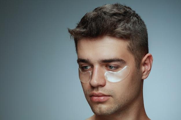 Szczegół portret profil młodego człowieka na białym tle na szarym tle studio. męska twarz z kolagenowymi plamami pod oczami. koncepcja zdrowia i urody mężczyzn, kosmetologii, pielęgnacji ciała i skóry. przeciw starzeniu.