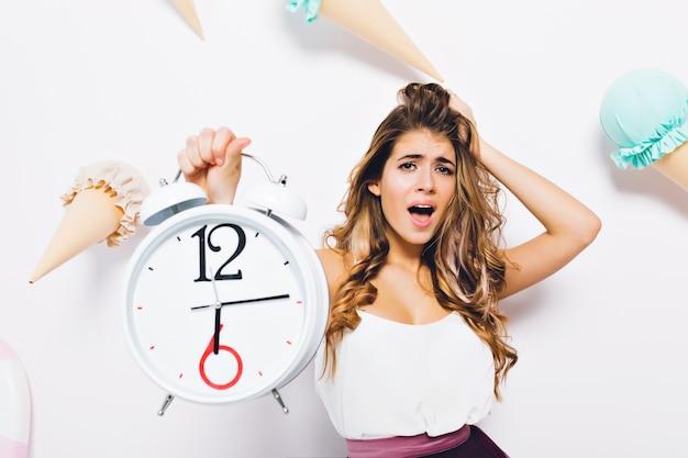 Szczegół portret przerażonej brunetki kobiety w stylowym stroju dotykając włosów i trzymając duży zegar. oszałamiająca młoda kobieta emocjonalnie pozuje na udekorowanej ścianie z lodami.