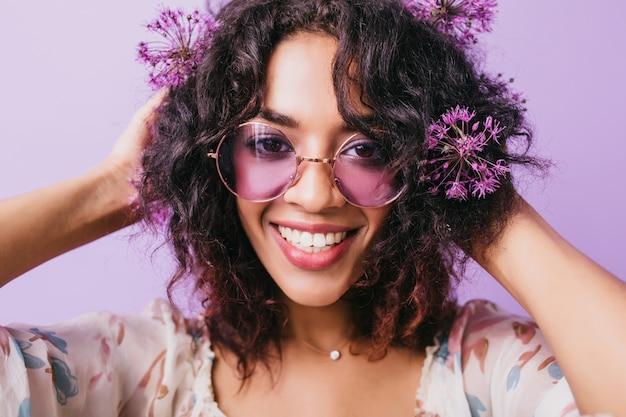 Szczegół portret przyjemnej afrykańskiej dziewczyny z falistymi czarnymi włosami. kryty zdjęcie uśmiechniętej modelki z fioletowymi aliumami.