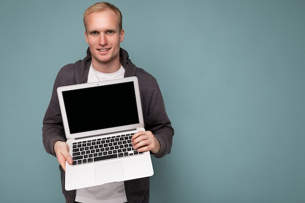 Szczegół portret przystojny blondyn trzyma komputer laptop patrząc na kamery na białym tle nad niebieskim tłem.