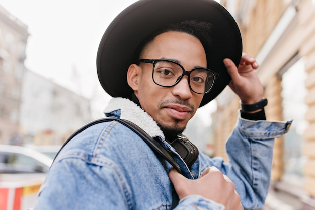 Szczegół portret przystojny mężczyzna afryki z krótką fryzurą pozowanie w modnym kapeluszu. plenerowe zdjęcie czarnego faceta w dobrym nastroju spędzającego czas w mieście w jesienny dzień.