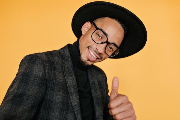 Szczegół portret przystojny murzyn z uroczym uśmiechem. dobrze ubrany afrykański facet nosi kapelusz i kurtkę.