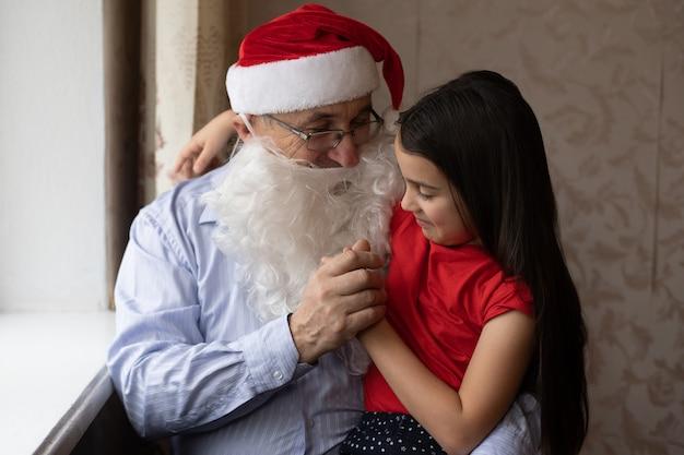 Szczegół portret radosnej dziewczyny przytulanie dziadka w nakrycia głowy. dziadek i wnuczka w czapkach świętego mikołaja