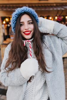 Szczegół portret romantycznej dziewczyny europejskiej o ciemnych włosach z słodkim lizakiem bożonarodzeniowym. zdjęcie całkiem kaukaski modelki w białych rękawiczkach i niebieskim kapeluszu, zabawy