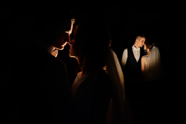 Szczegół portret romantycznej pary sylwetka z podświetleniem w nocy. kreatywny pomysł na fotografię ślubną w nocy. sylwetka panny młodej i pana młodego, oświetlone przez światła.
