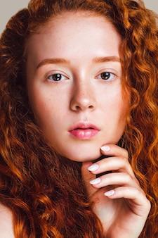 Szczegół portret rudej dziewczyny z kręconymi włosami, małymi piegami i brązowymi oczami. piękny model zagląda do aparatu. wyretuszowane zdjęcie zostało nakręcone w studio. skóra bez makijażu