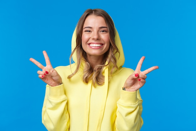 Szczegół portret śliczna głupia blond europejska kobieta w żółtej bluzie z kapturem