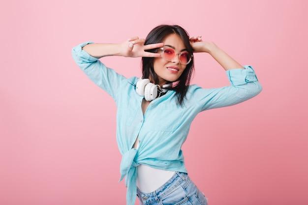 Szczegół portret stylowej azjatyckiej młodej kobiety nosi eleganckie okulary i bawełnianą koszulę. urocza dziewczyna hiszpanin z czarnymi lśniącymi włosami relaksujący w różowym pokoju.
