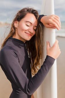 Szczegół portret szczęśliwa uśmiechnięta piękna dziewczyna z długimi włosami i czarującym uśmiechem stoi w słońcu na brzegu oceanu i zachowuje spokój. aktywna sportowa kobieta w słoneczną pogodę z deską surfingową