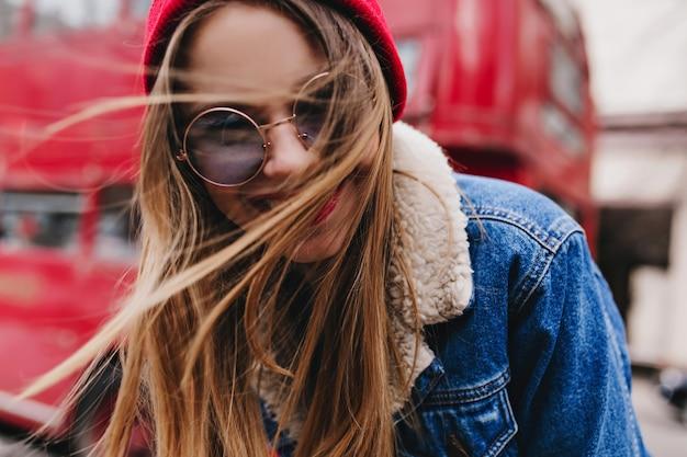 Szczegół portret uroczej białej kobiety zabawy w dobry dzień wiosny. czarująca kaukaska dziewczyna w stylowej dżinsowej kurtce śmiejąca się w pobliżu czerwonego autobusu.
