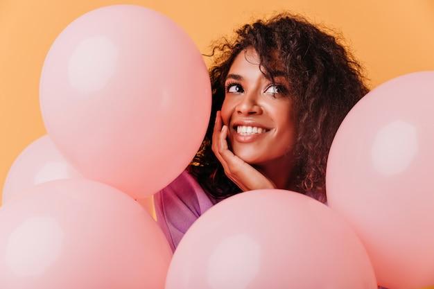 Szczegół portret uroczej czarnej kobiety zabawy na przyjęciu urodzinowym. urocza afrykańska dziewczyna pozuje z różowymi balonami.