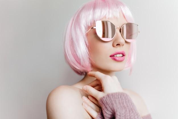 Szczegół portret uroczej damy z różowymi ustami, pozowanie w okularach i peruke. atrakcyjna biała dziewczyna w krótkiej peruce stojącej na jasnej ścianie.