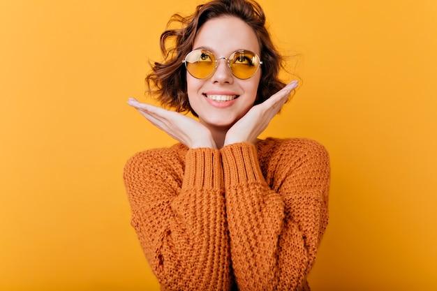 Szczegół portret uroczej dziewczyny roześmiany w akcesoria vintage. kryty zdjęcie ślicznej uśmiechniętej kobiety z falistą fryzurą, zabawy.