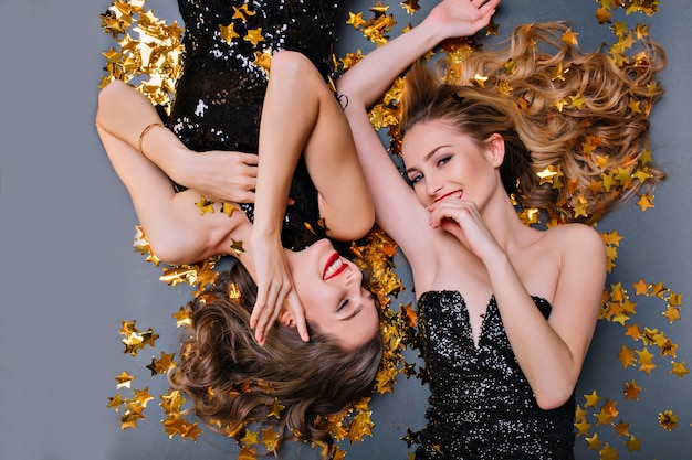Szczegół portret wesoły młodej kobiety leżącej na konfetti gwiazdy po imprezie. śmiejąca się europejska blondynka pozuje na podłodze z przyjacielem podczas uroczystości.