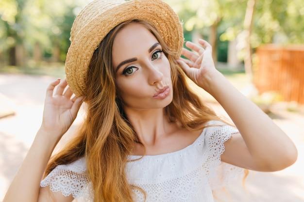 Szczegół portret wspaniałej długowłosej dziewczyny z zielonymi oczami pozuje z przyjemnością w słoneczny dzień. zdjęcie jasnowłosej pani z całowaniem wyrazem twarzy na sobie pierścień.