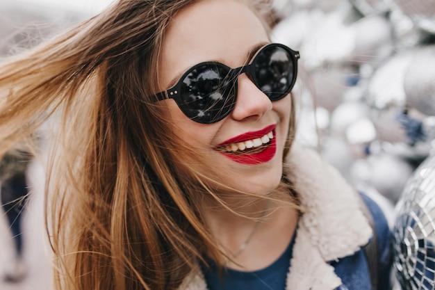 Szczegół portret wspaniałej kobiety w czarnych okularach z kulkami disco. zdjęcie śmiejącej się beztroskiej dziewczyny z jasnym makijażem, zabawy