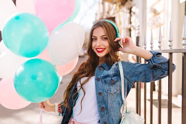 Szczegół portret wspaniałej kręconej dziewczyny w dżinsowej kurtce z urodzinowymi balonami na zewnątrz.