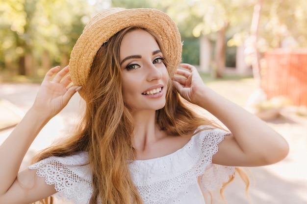 Szczegół portret wyrafinowanej pani w modnym kapeluszu lato uśmiechając się. zewnątrz zdjęcie całkiem długowłosej dziewczyny na sobie elegancki pierścionek i białe ubrania.