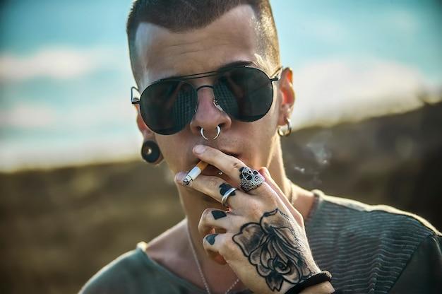 Szczegół portret wytatuowanego młodego chłopca z okularami przeciwsłonecznymi, palącego papierosa