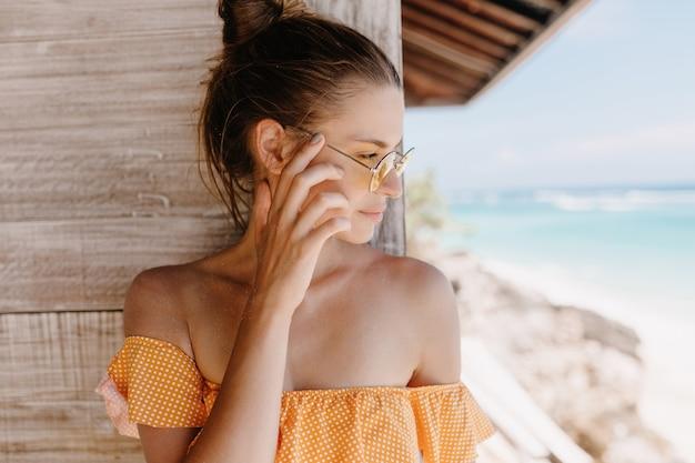 Szczegół portret zamyślony brunetka dziewczyna stojąca na drewnianej ścianie. odkryty strzał wyrafinowanej opalonej pani w pomarańczowych ubraniach, odwracając wzrok.
