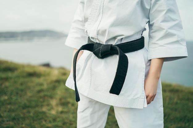 Szczegół potomstwa młodzi karate atlety czarny pasek i kimono