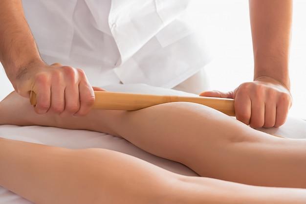 Szczegół ręki masuje ludzkiego łydkowego mięsień.