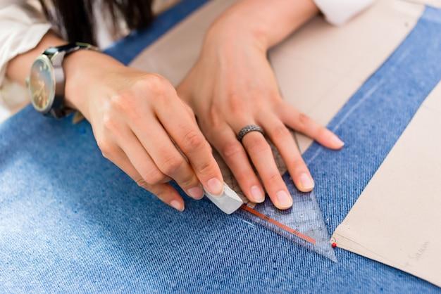 Szczegół ręki z nożycami przy krawieckim sklepowym tnącym płótnem