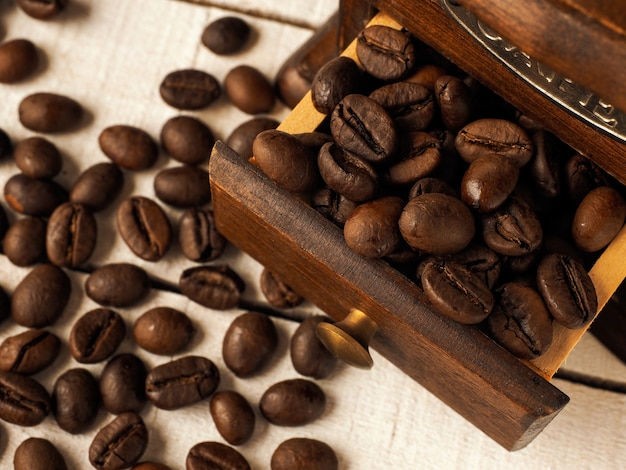 Szczegół rocznika młynek do kawy młyn z ziaren kawy na ciemnym i jasnym tle drewnianych.