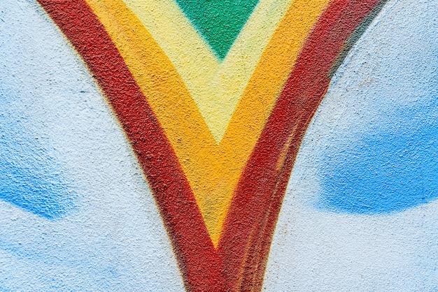 Szczegół rysunku na opuszczonej ścianie, z różnymi kolorami i zabawnymi kształtami w tle.