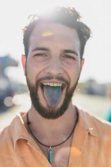 Szczegół słodki facet z niebieskim językiem