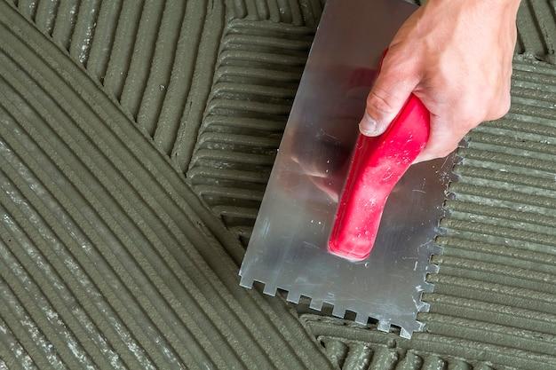 Szczegół szczegół instalacji płytek podłogowych. majsterkowanie, remont. ręka pracowników z karbowanym pływakiem do płytek. klej do płytek ceramicznych, zaprawa.
