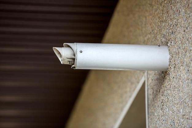 Szczegół szczegół nowej białej sztywnej metalowej rury wentylacyjnej zainstalowanej na zewnętrznej ścianie domu