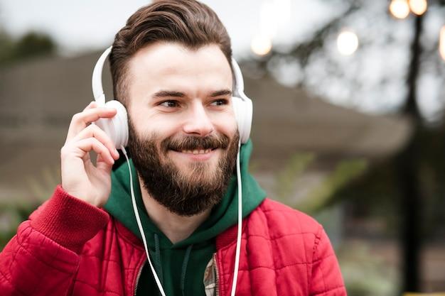 Szczegół szczęśliwy facet ze słuchawkami i czerwona kurtka